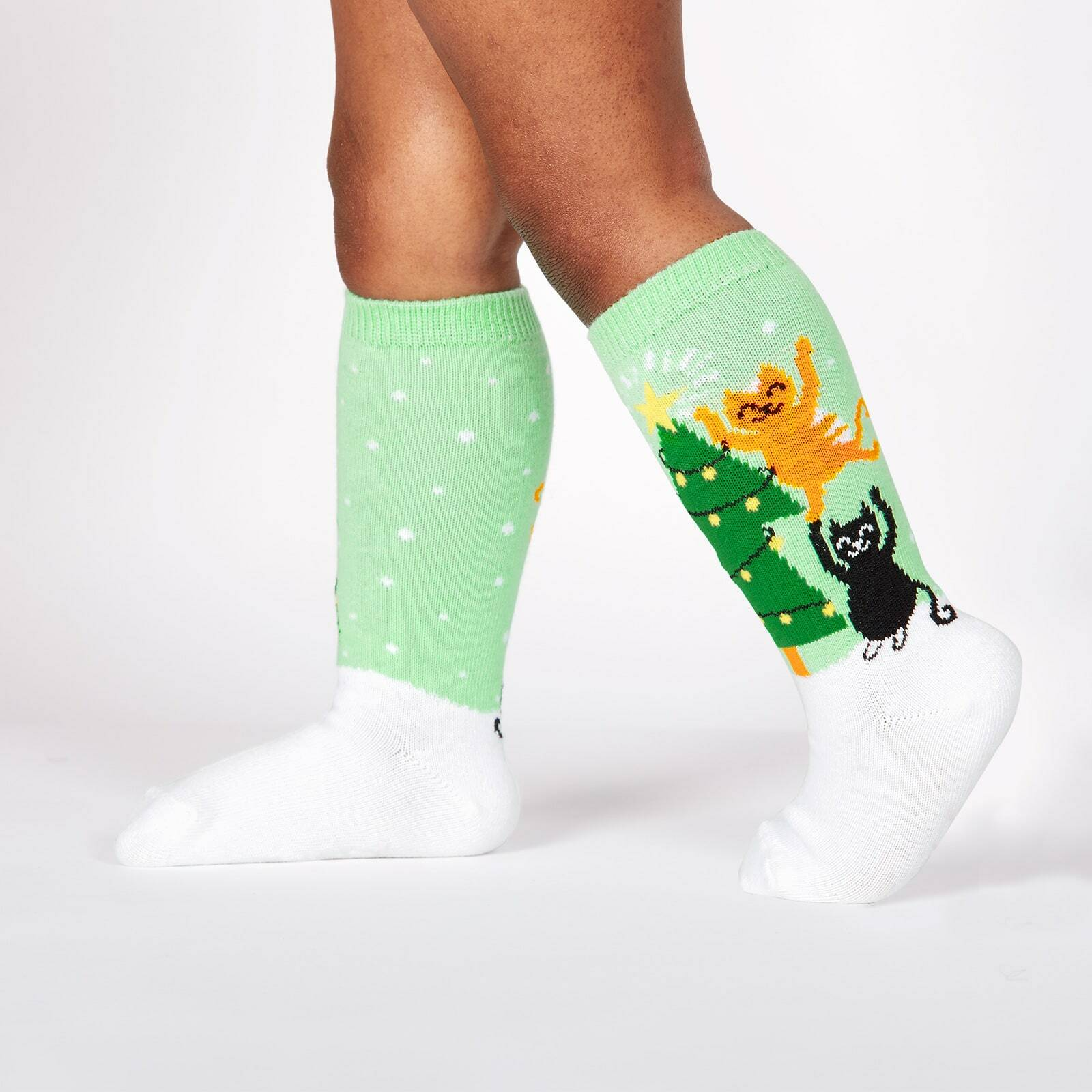 model wearing Naughty or Nice? - Winter Cats Decorating Christmas Tree Snow Knee High Socks Green - Toddler